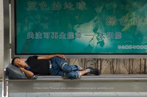 Man sleeping at bus stop, Shanghai.